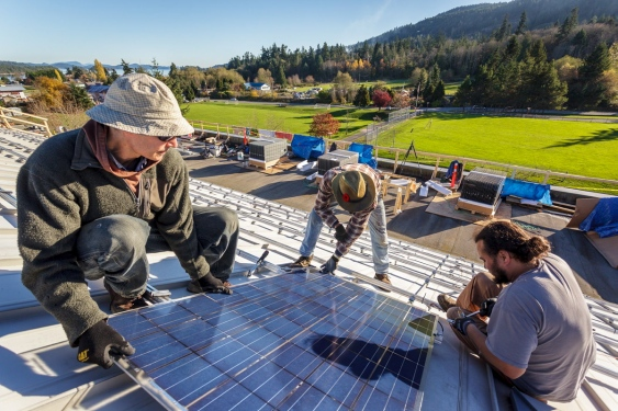 Electrical engineer Will Andrew, left, installer Lane Gromme and project manager Kjell Liem install solar panels on the roof of Gulf Islands Secondary School. The 21-kilowatt project went live in December.   Photograph By Ron Watts, Photo courtesy of ronwattsphoto